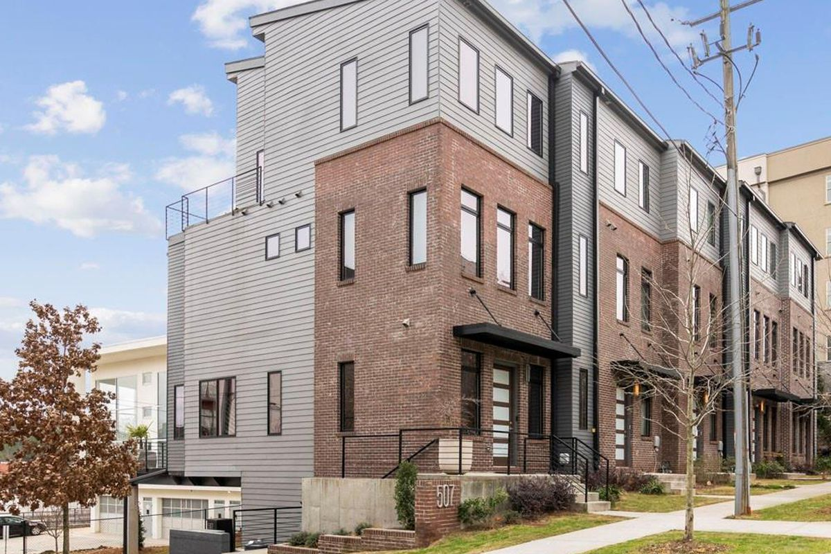 A small block of tall townhomes with brick and cement siding.