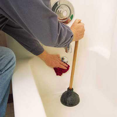 Person using a plunger on a clogged bathtub drain.