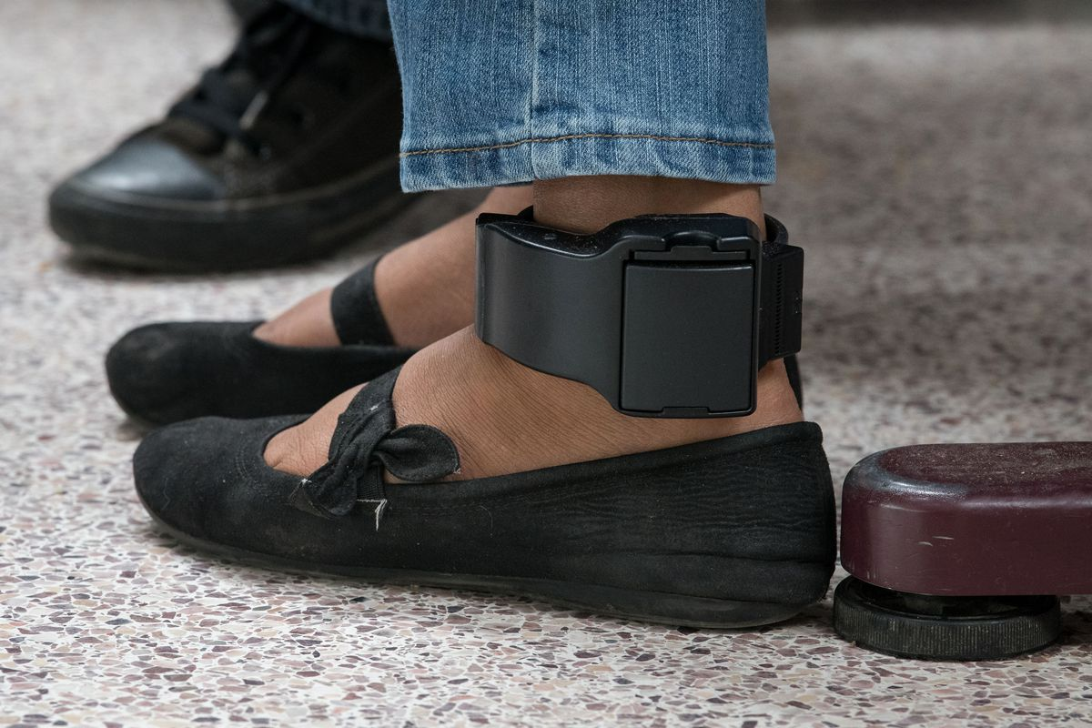 An ankle monitor strapped to a woman's ankle.