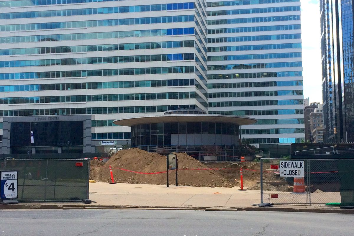 The construction site at Love Park in Philadelphia, looking past the fences toward the Welcome Center, a round, midcentury modern structure.