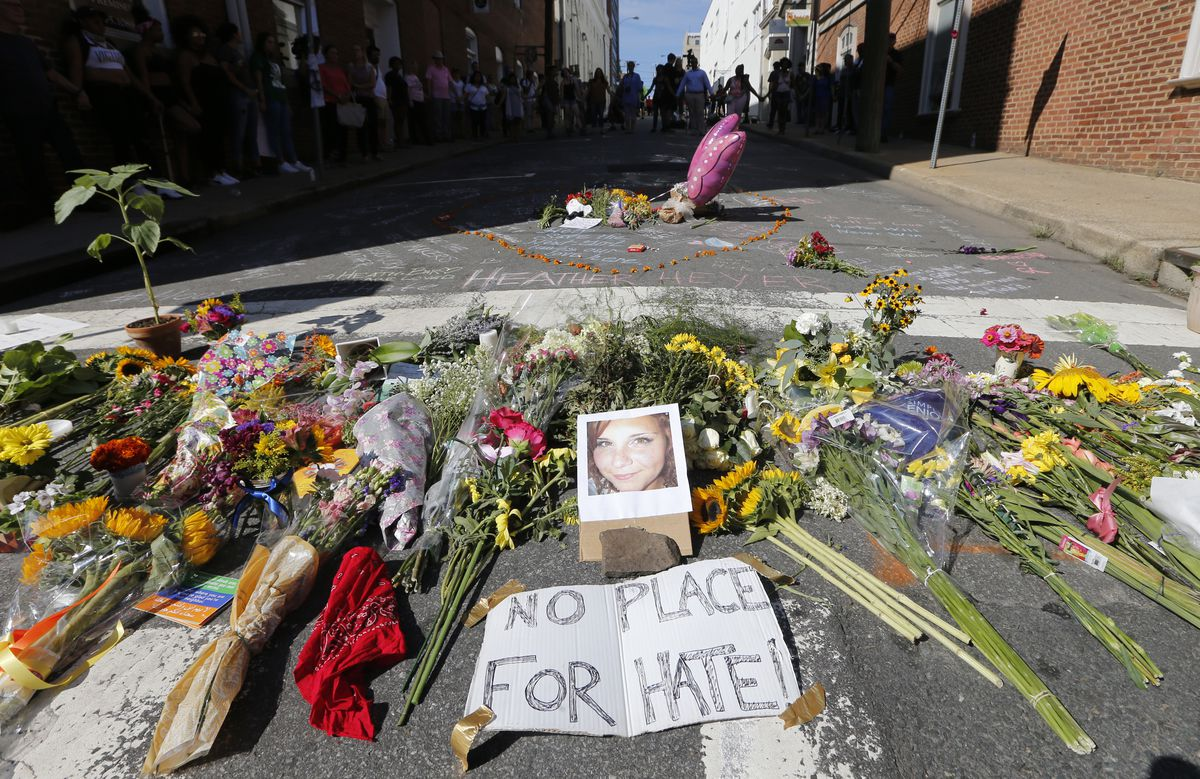 A makeshift memorial of flowers and a photo of victim, Heather Heyer, sits in Charlottesville, Virginia on Sunday. Heyer died when a car rammed into a group of people who were protesting the presence of white supremacists who had gathered in the city for