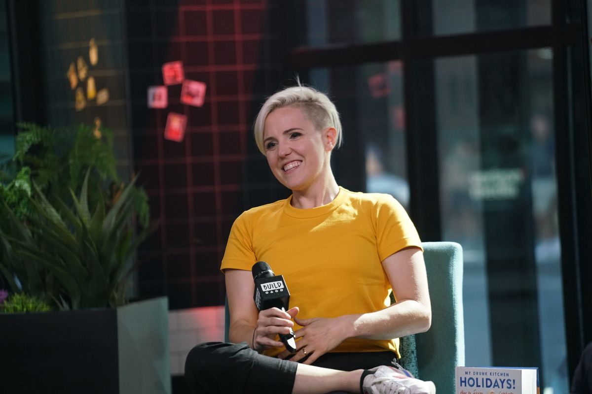 Hannah Hart wearing a yellow top, holding a microphone at a media event.