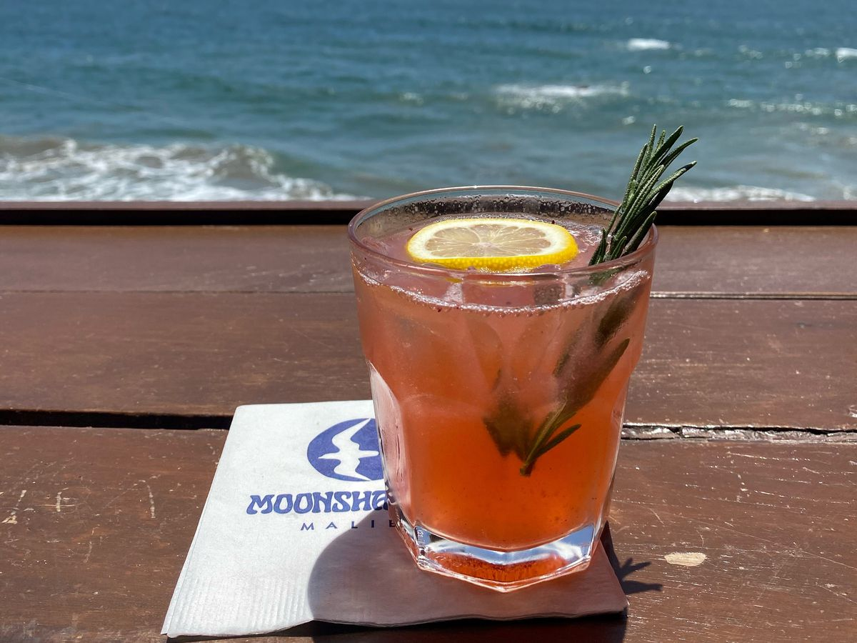 A pink drink sits in a short glass topped with a lemon slice and a sprig of rosemary, overlooking a gorgeous view of the pacific ocean.