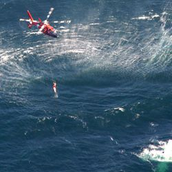 In this photo provided by the U.S. Coast Guard via the California Highway Patrol, a Coast Guard helicopter lowers a rescue swimmer to a downed aircraft in Morro Bay off California's central coast Sunday, Sept. 9, 2012. Thirty-six-year-old Stanford Shaw says he and his 77-year-old father, Stanley, were flying from Southern California to British Columbia on Sunday when the single engine of their Cessna 185 lost power. The plane sank after the two were rescued.