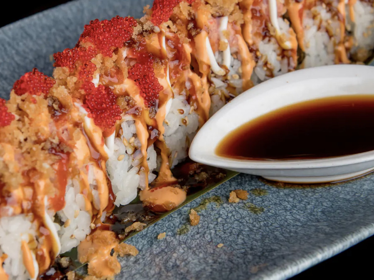 A long, uncut sushi roll sits atop a blueish-green plate, accompanied by a small dish filled with soy sauce