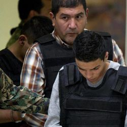 """The alleged leader of a faction of the hyper-violent Zetas cartel, Ivan Velazquez Caballero, known as """"El Taliban,""""  is escorted to a media presentation at the Mexican Navy's Center for Advanced Naval Studies in Mexico City,Thursday, Sept. 27, 2012. Velazquez Caballero allegedly has been fighting a bloody internal battle with top Zetas' leader Miguel Angel Trevino Morales, and officials have said the split was behind a recent surge in massacres and shootouts, particularly in northern Mexico."""
