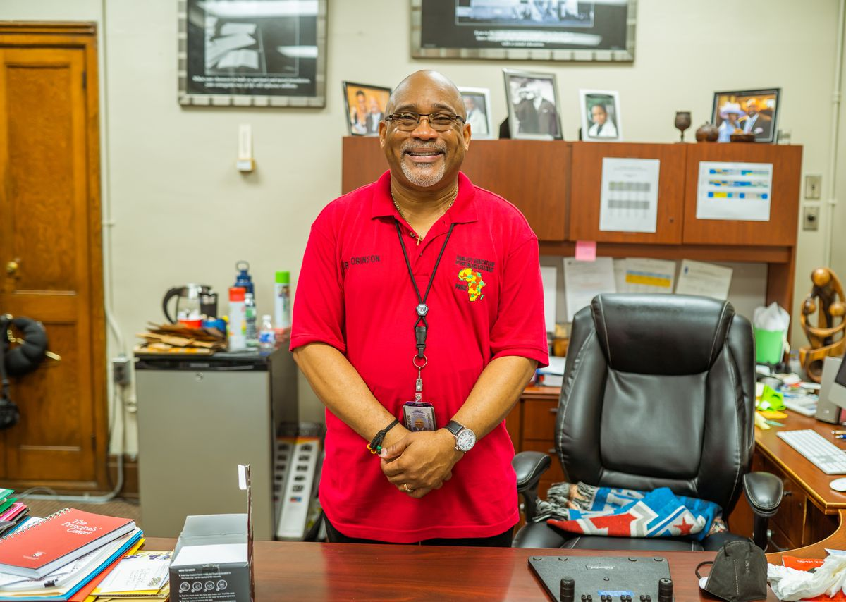 Dr. Jeffery Robinson, the principal of Paul Robeson Malcom X Academy, poses for a portrait at his desk while wearing a red polo shirt.