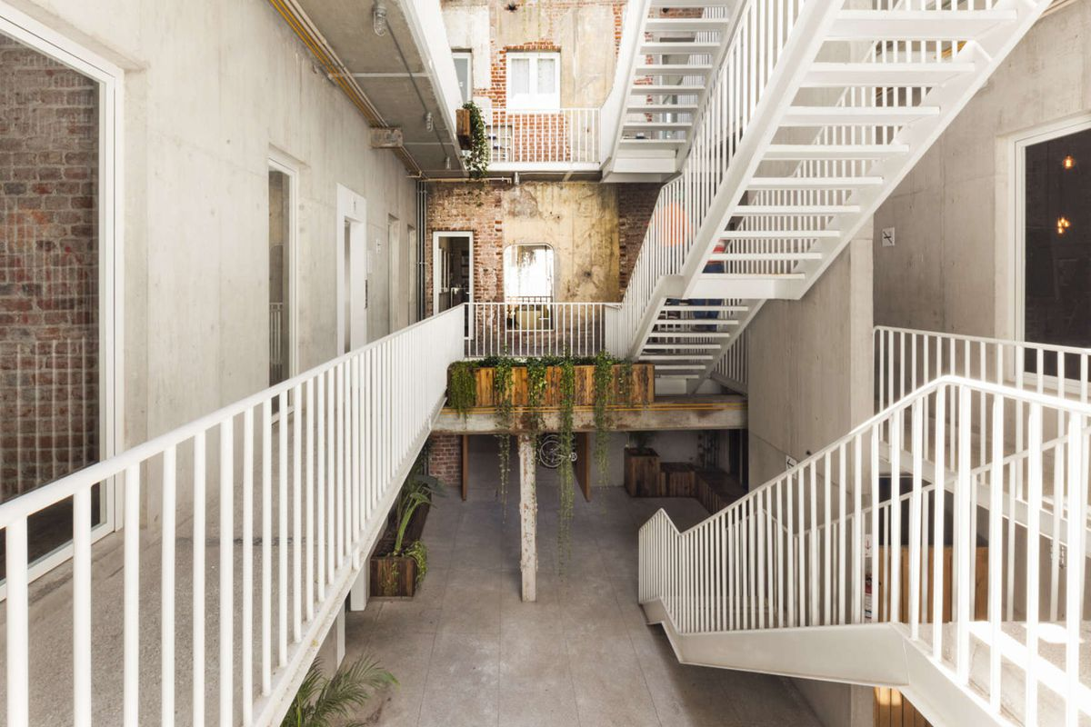Interior shot of a light-filled atrium where the walls are exposed brick and concrete, and a series of white metallic staircases connects the different levels.