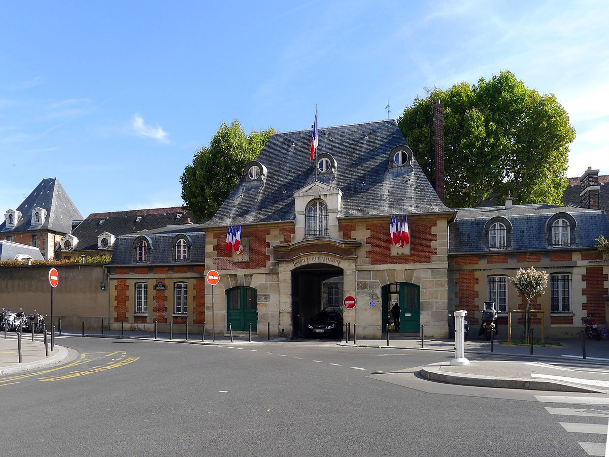 An exterior view of the Hospital Saint-Louis in Paris. The facade is tan with red and a grey roof. There is a courtyard in front of the hospital.