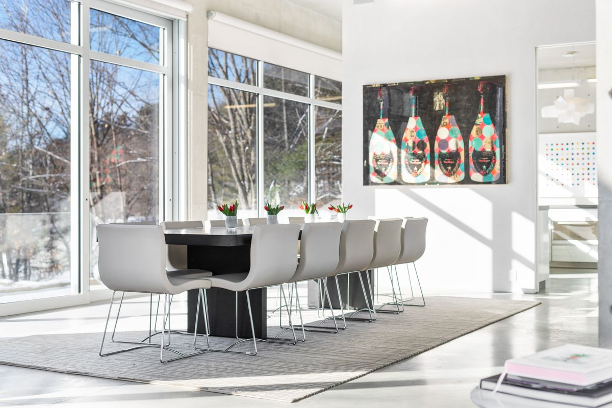 A dining room has a modern table for 12 on a gray rug. The room features tall ceilings and large floor-to-ceiling windows.