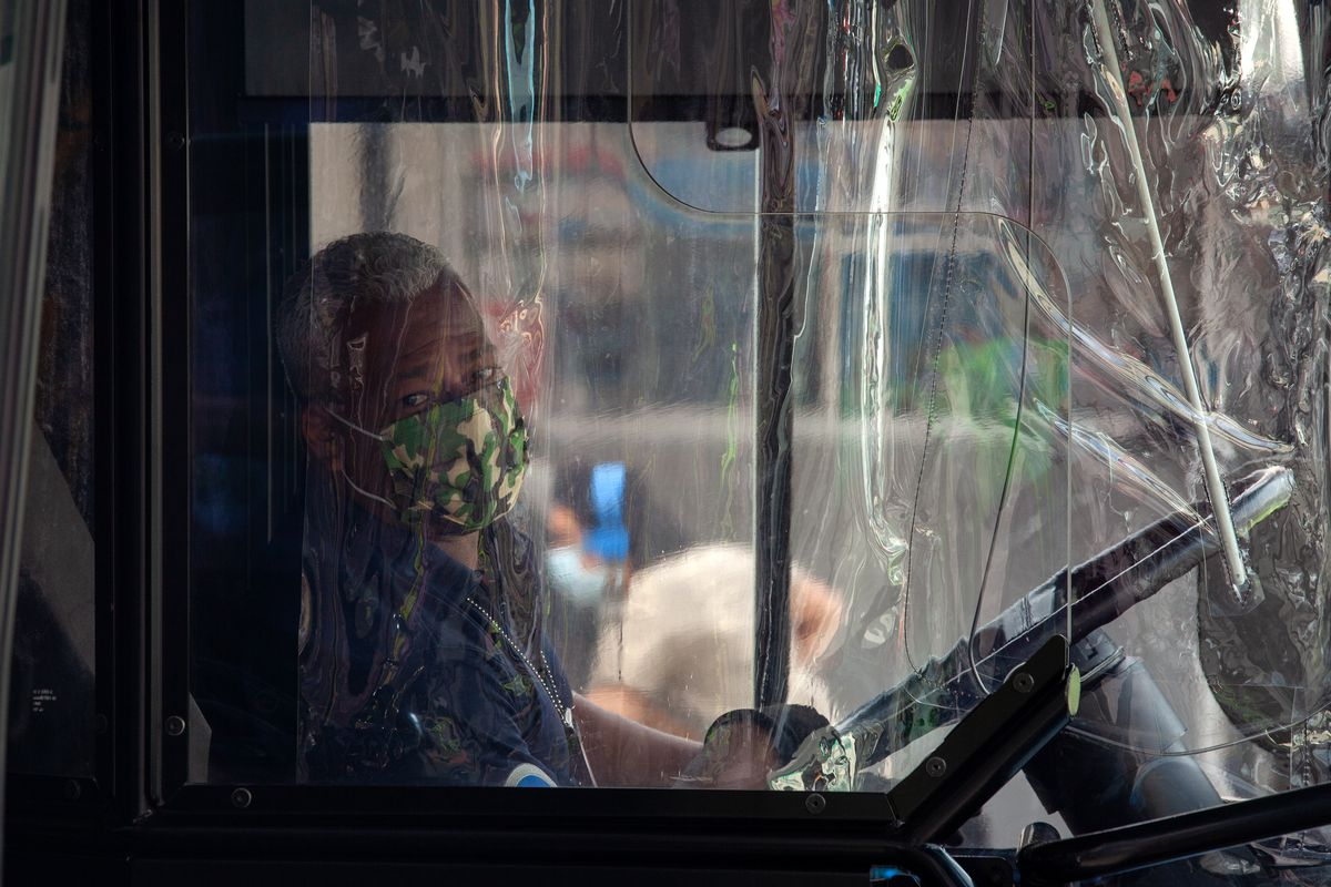 A driver wears a mask behind a plastic shield on an MTA bus in Brooklyn, Oct. 1, 2020.