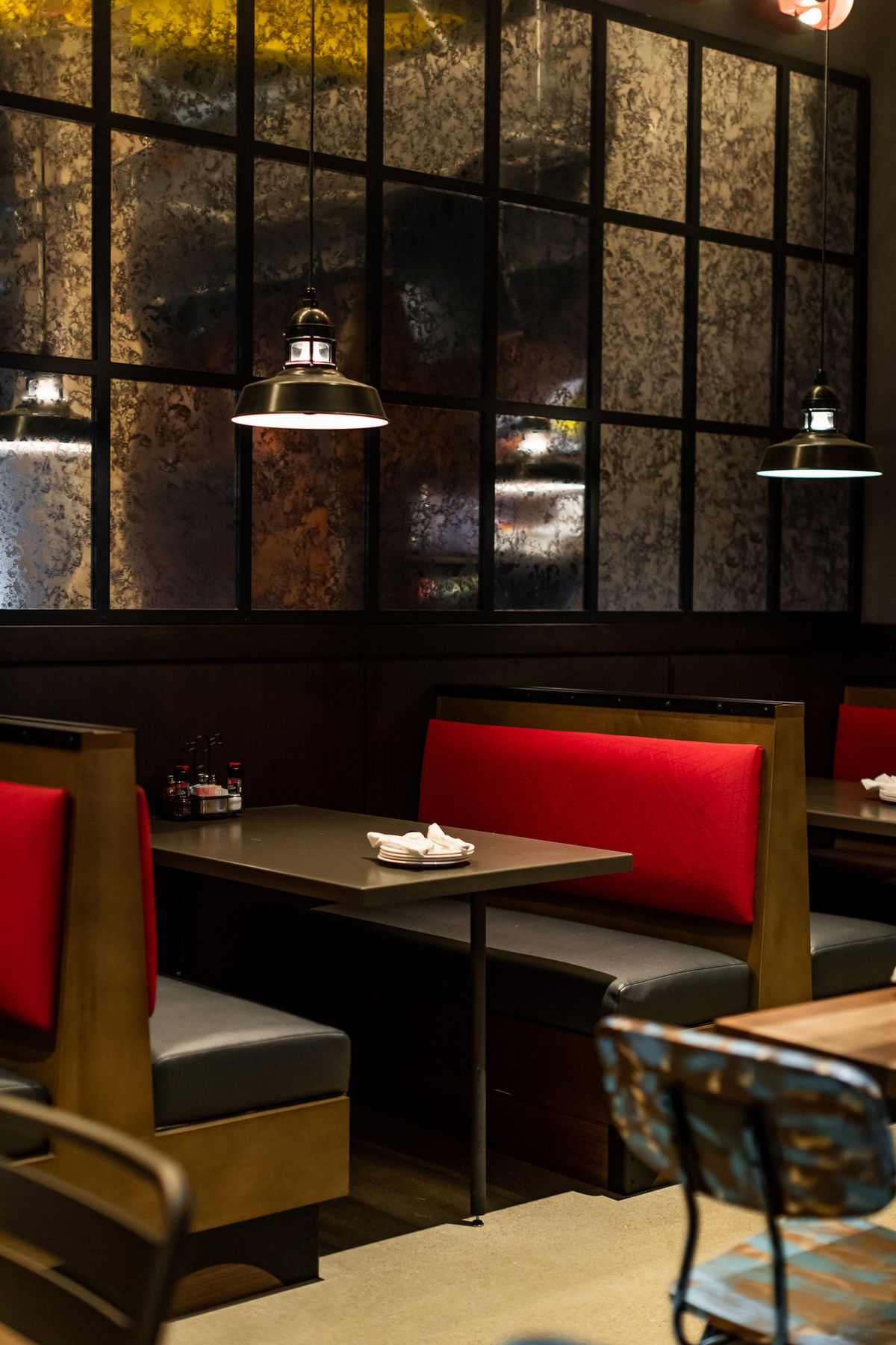 Wooden booths with pendant lights and red and white upholstery at Buddy's in downtown Detroit.