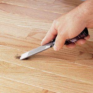 Person scraping a shallow burn mark on a polyurethane floor.