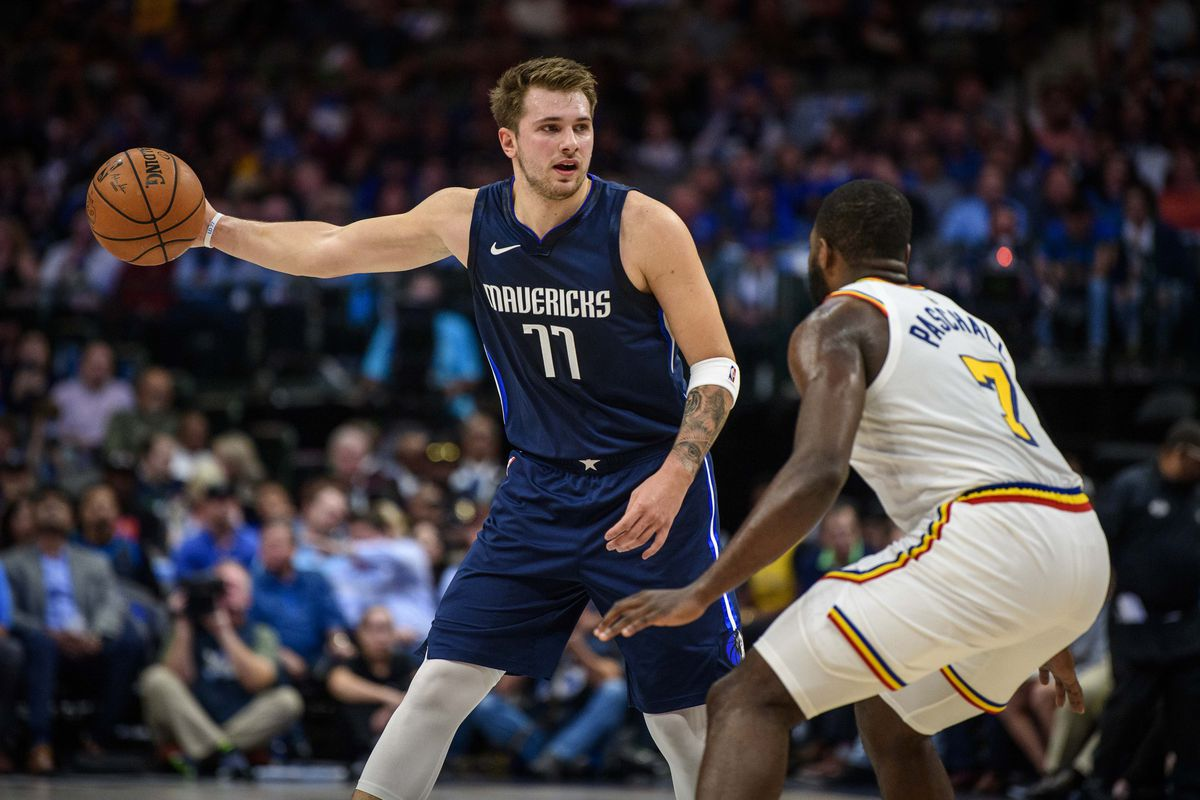 Dallas Mavericks forward Luka Doncic does a no look pass as Golden State Warriors forward Eric Paschall defends during the first quarter at the American Airlines Center.