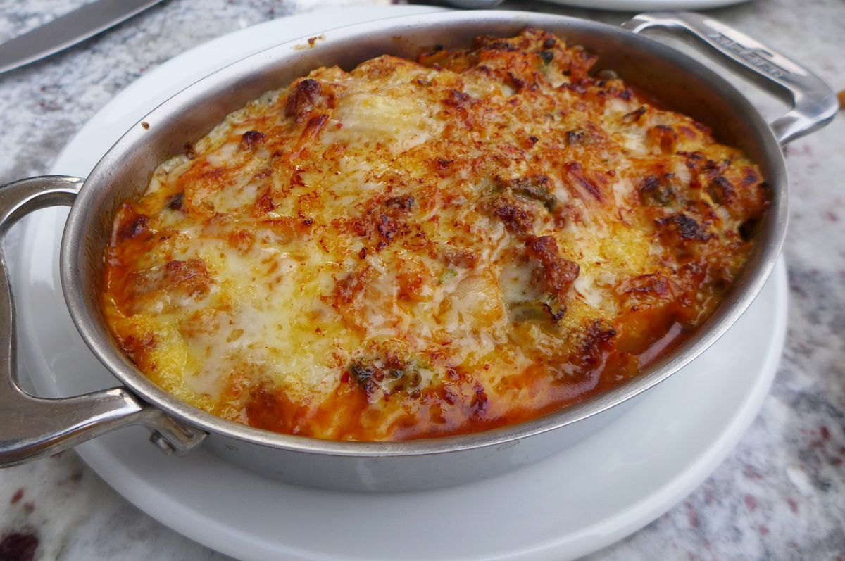 An oblong pan with cheese, tomato sauce, and crumbled sausage visible on top.