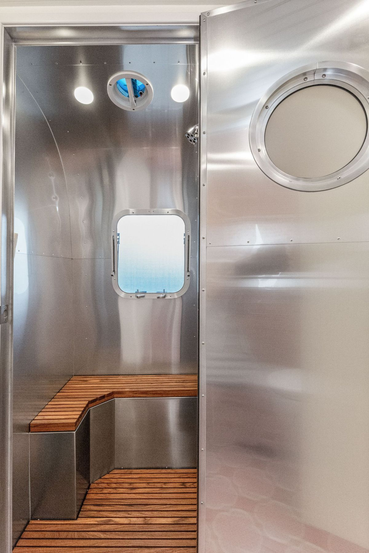 The shower area has aluminum walls, a square porthole window, and a wooden seat and flooring.