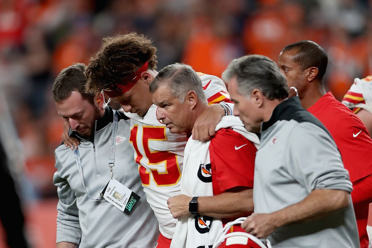 Quarterback Patrick Mahomes of the Kansas City Chiefs is escorted off the field after an injury in the first half against the Denver Broncos in the game at Broncos Stadium at Mile High on October 17, 2019 in Denver, Colorado.