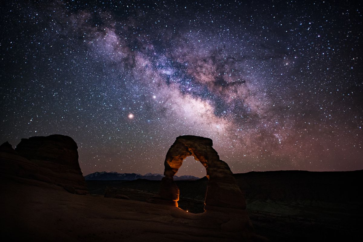 Delicate Arch looms in front of the night sky in Arches National Park.