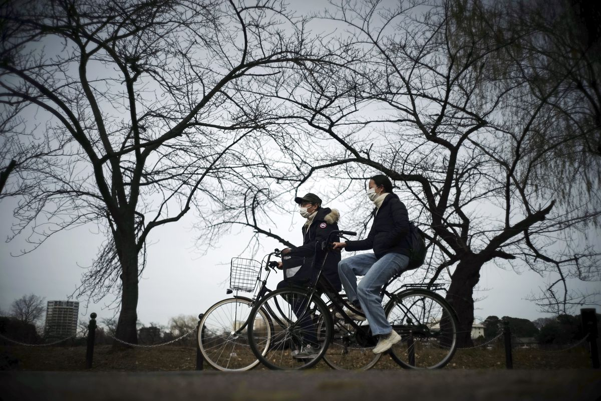 People wearing protective masks to help curb the spread of the coronavirus ride bicycles along the Shinobazu Pond in Tokyo Monday, Jan. 11, 2021.