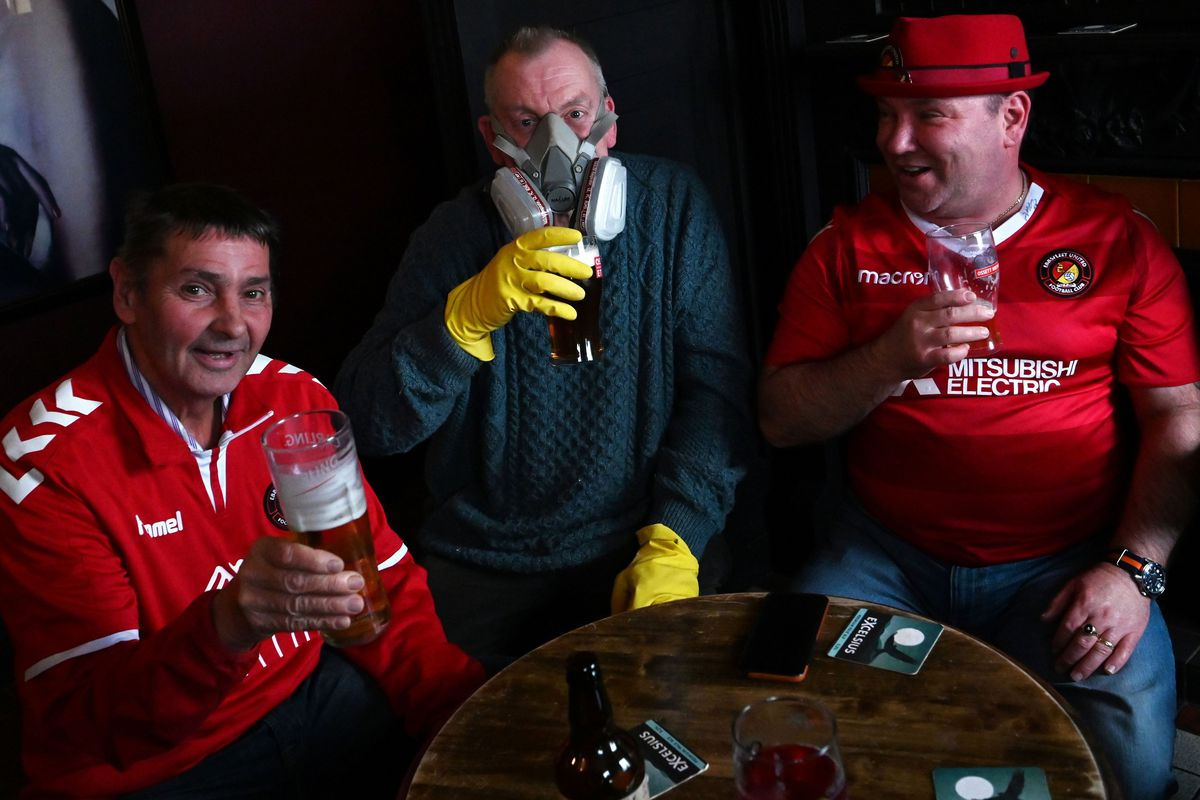 football fans drink beers in The Three Pigeons pub in Halifax, northern England