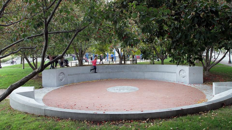 A circular memorial built into a park, with a taller wall on one end of the circle.
