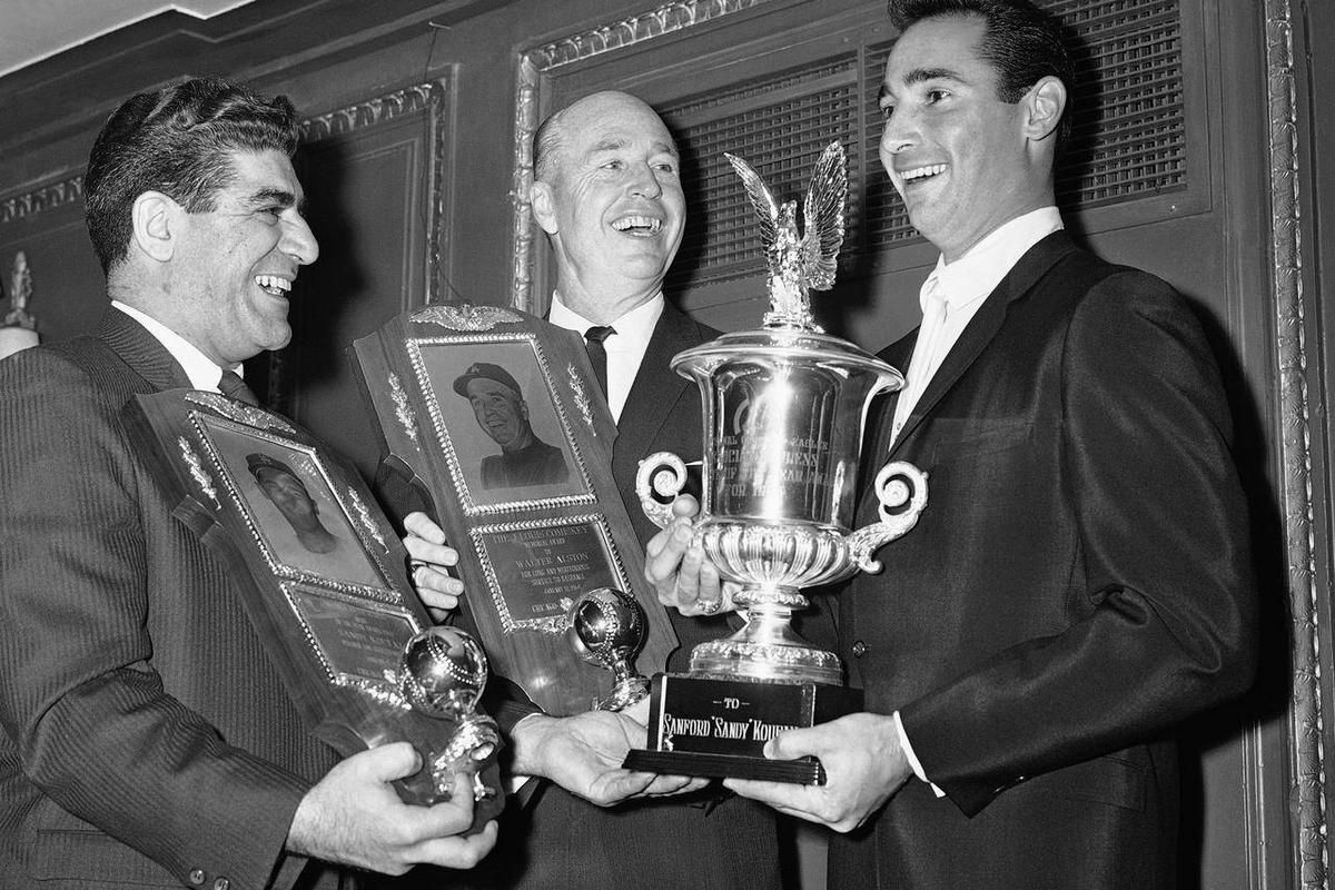 FILE - In this Jan. 12, 1964, file photo, Los Angeles Dodgers pitcher Sandy Koufax, right, stands with manager Walt Alston, center, and Associated Press sportswriter Joe Mooshil in Chicago during a Chicago baseball writers' awards dinner. Mooshil, who bec