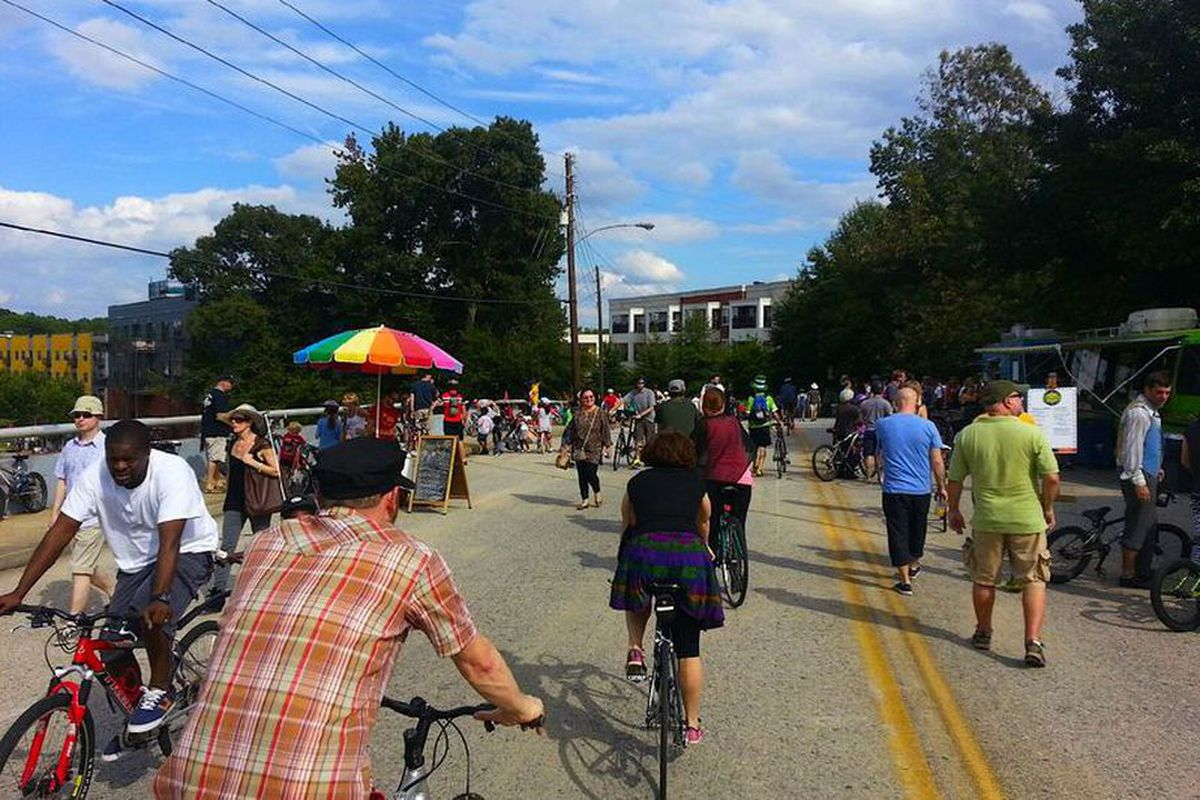 People riding bikes and walking and food trucks on a busy Atlanta street.
