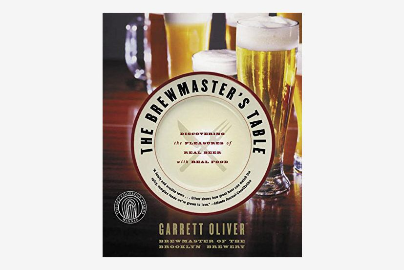 "The cover of ""The Brewmaster's Table"" with the title on a white plate and beer glasses in the background"