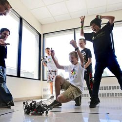 Instructor Morgan Reynolds, left, and students Carson Crook, center front, and Blake Ferris, top right, react as they and others watch a robot battle Friday, July 22, 2011, at the Warnock Engineering Building at the University of Utah.