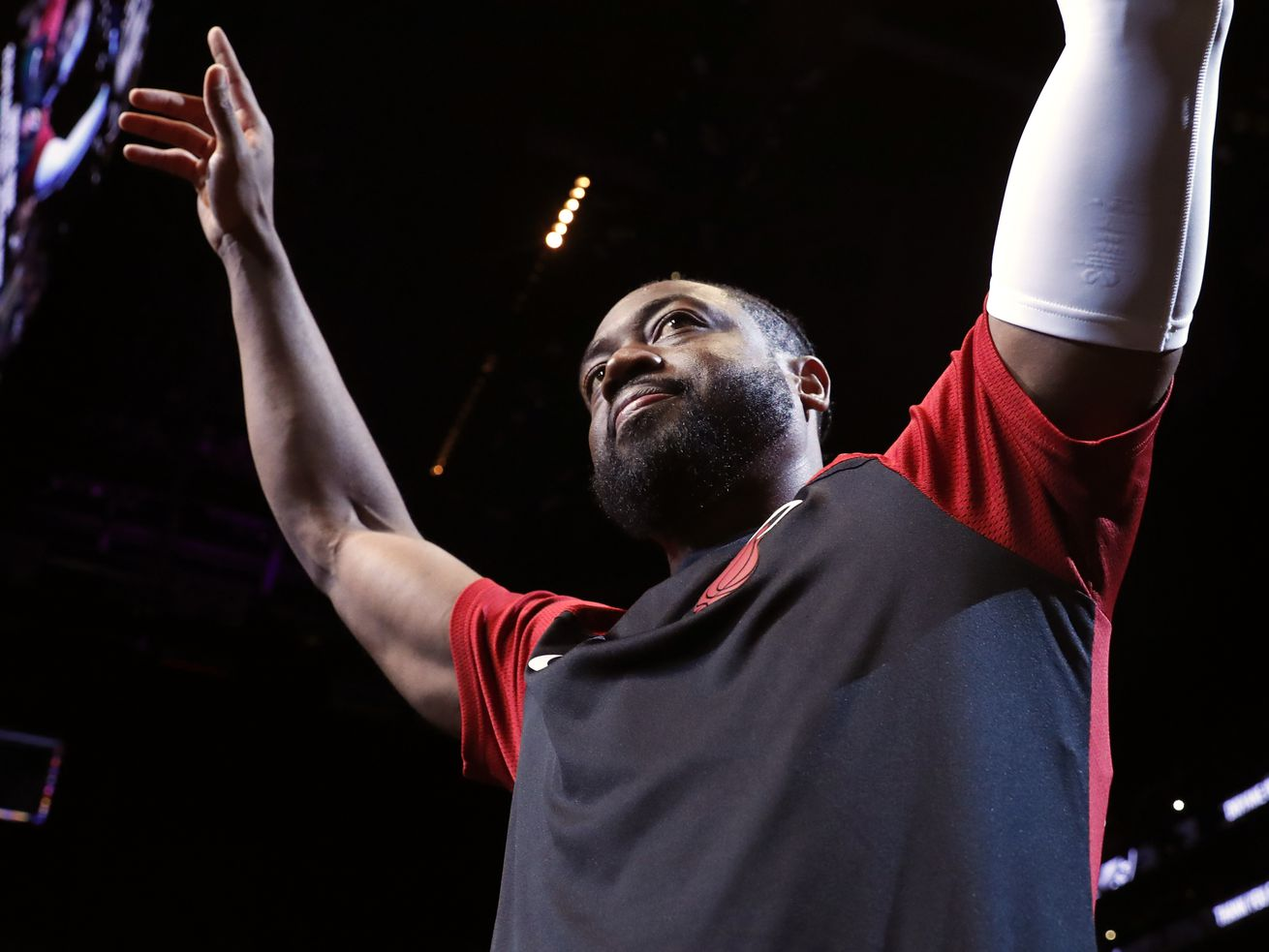 Miami Heat guard Dwyane Wade (3) acknowledges cheers from the crowd before the start of the final NBA basketball game of his career, against the Brooklyn Nets in New York. (AP Photo/Kathy Willens)