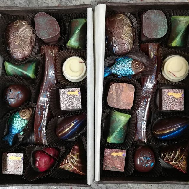 Overhead view of two boxes of fancy chocolates, painted with brightly colored and metallic accents