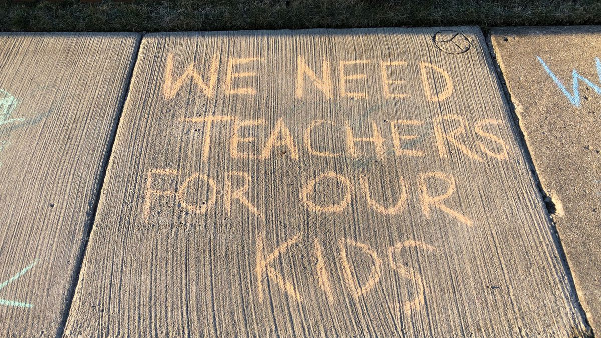 """A chalk message on a sidewalk. """"We need teachers for our kids."""""""