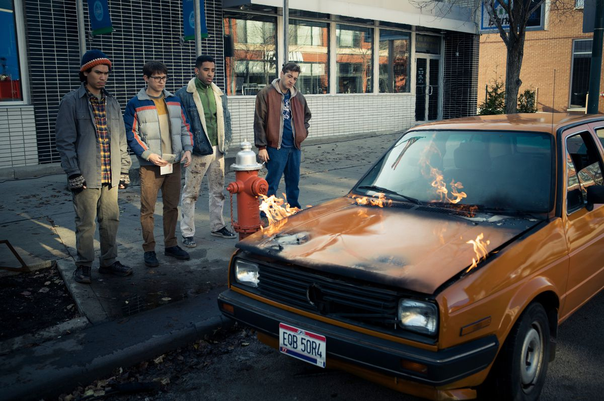 Cherry and his crew stand next to an orange car as the hood catches on fire