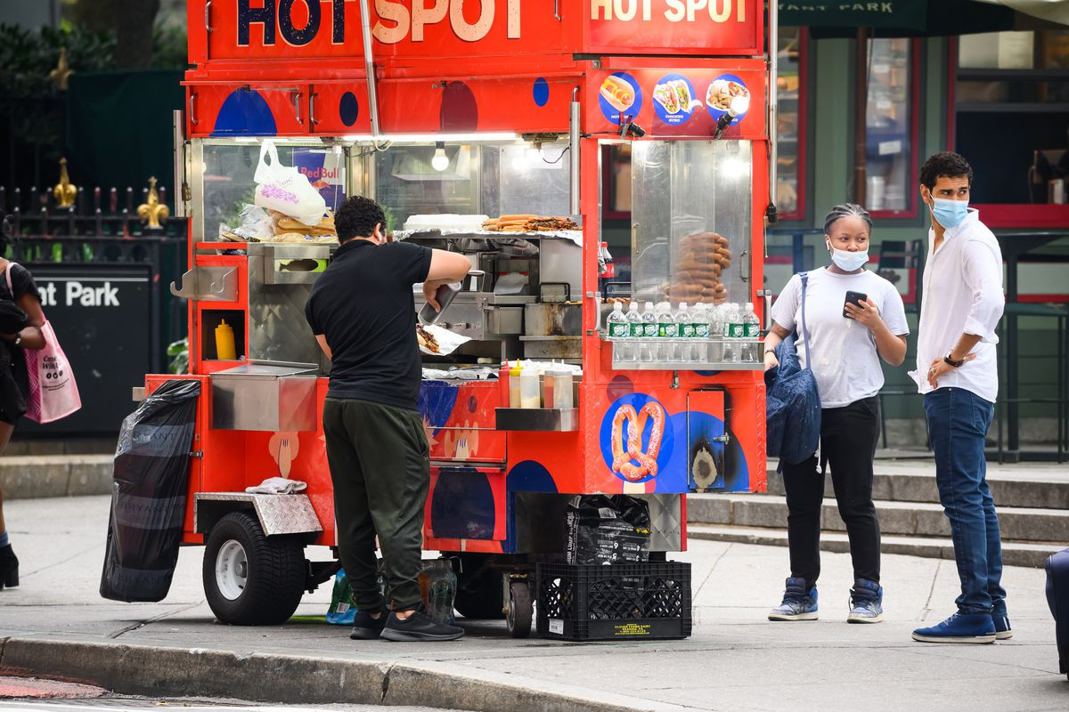 People wear protective face masks near a food truck in Bryant Park as the city continues Phase 4 of re-opening following restrictions imposed to slow the spread of coronavirus on August 13, 2020 in New York City.