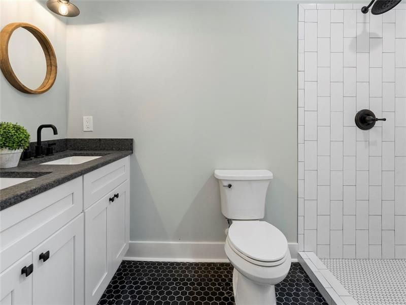 A master bathroom with black tiling and a white shower at right.