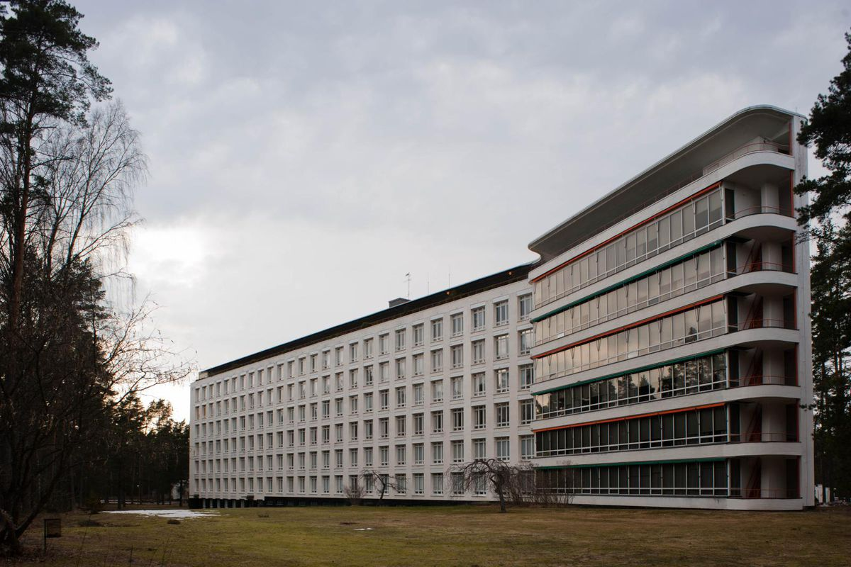 Large white hospital building with many windows and balconies.