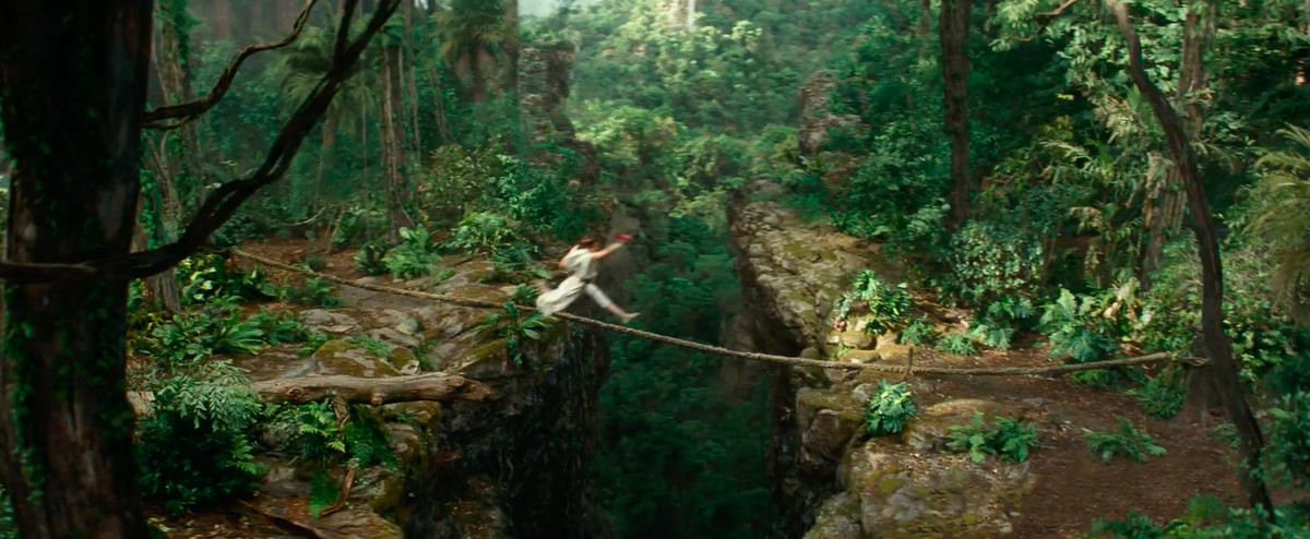 rey jumps across a chasm in the jungle