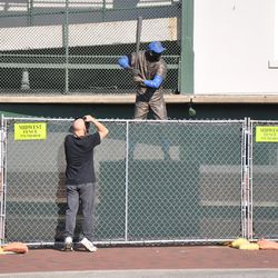 Taking a photo of the Ernie Banks statue over the construction fence
