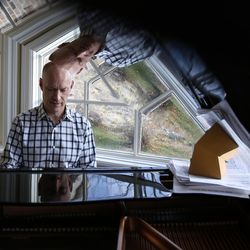 Jon Schmidt is reflected in his piano as he sits and plays in his home in Provo on Friday, Nov. 24, 2017.