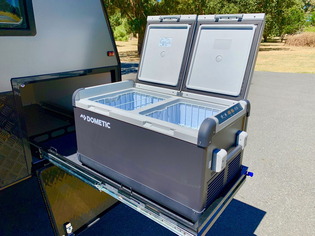 A Dometic fridge sits on a slide-out frame on the trailer. The fridge is gray with a white top and one section for freezer items.