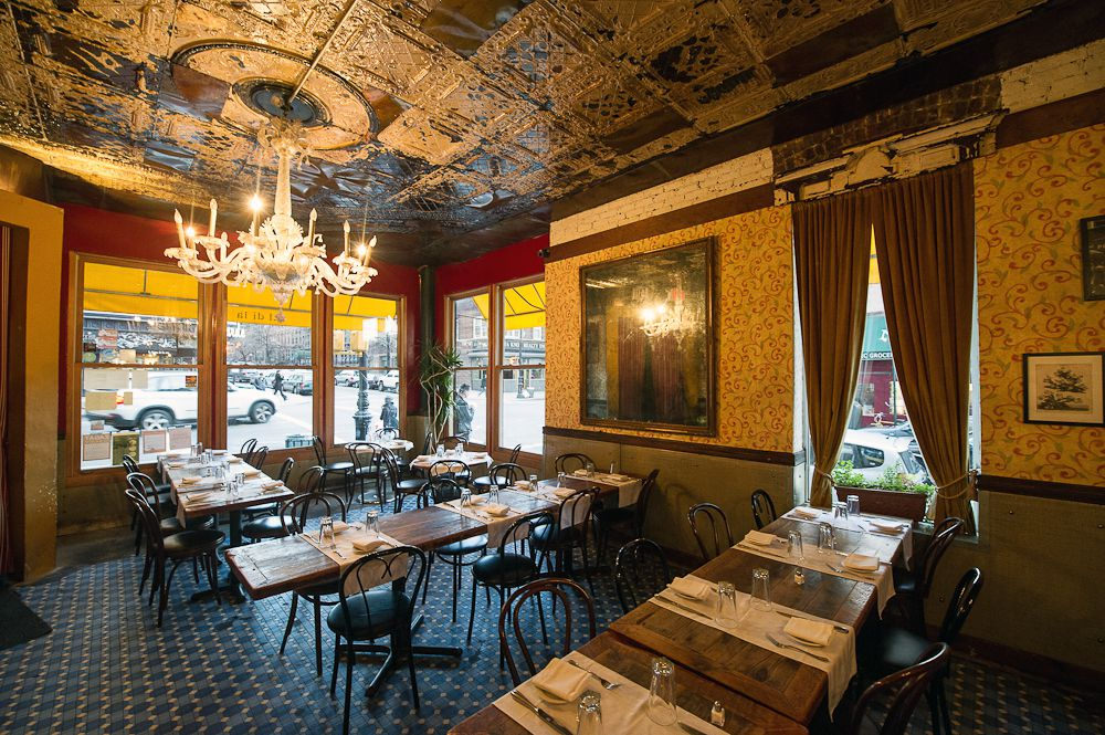 The dining room at Al Di La, with a chandelier, dining tables, and curtained windows