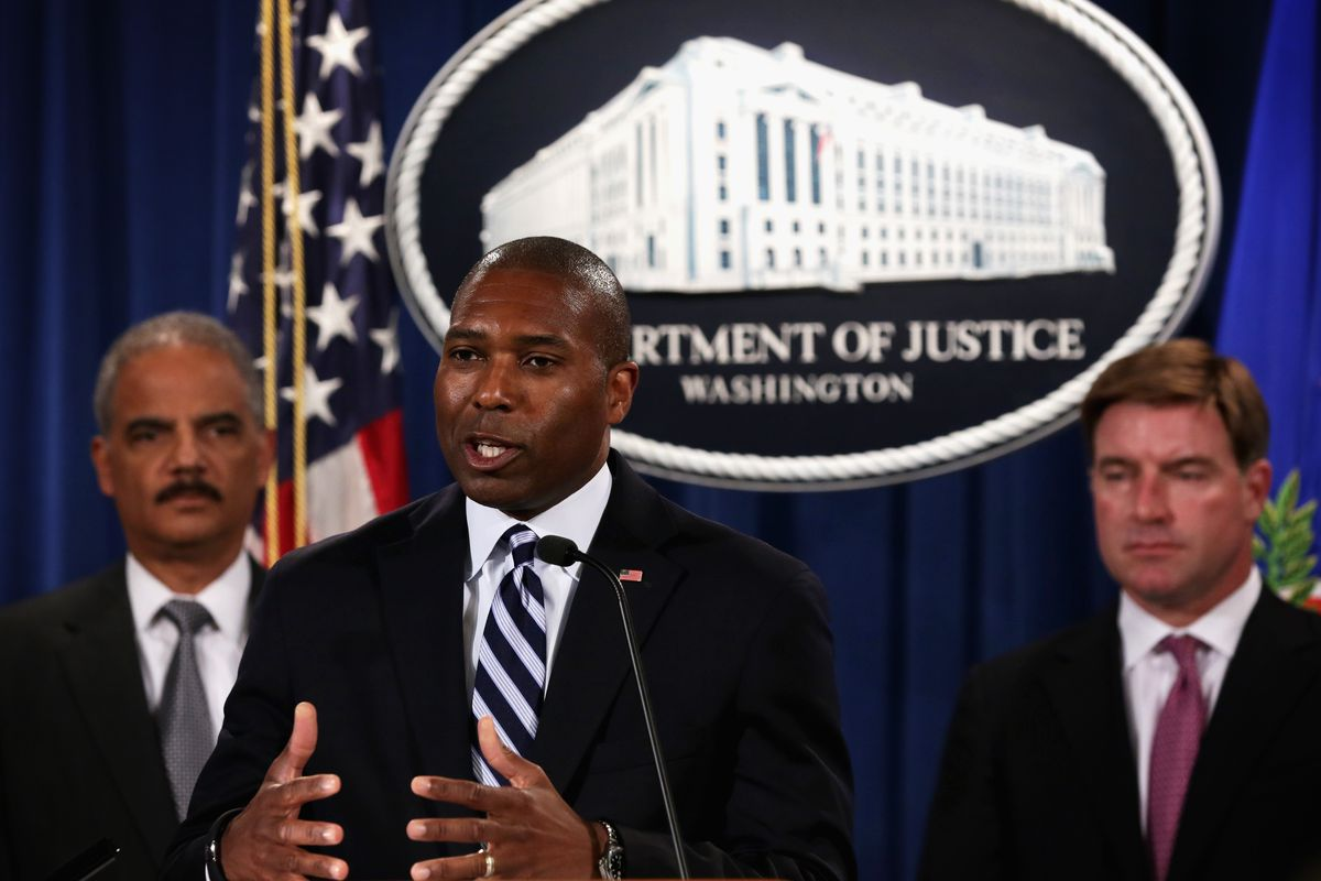 Tony West stands in front of the Department of Justice logo
