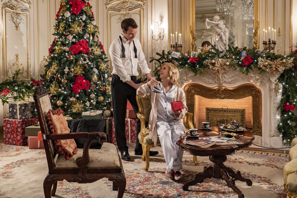 a lush decorated palace room where Queen Amber sits. King Richard stands behind here. There is a Christmas tree and a roaring fireplace. Amber is wearing silky silver pjs and is pregnant. Richard is in a suit, tie undone.