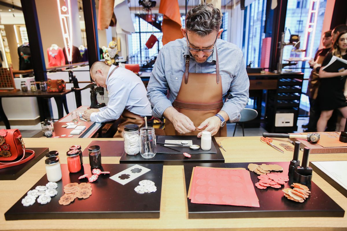 Two men wearing leather aprons stand in Coach's open workshop, creating flower appliques to punch onto vintage bags.