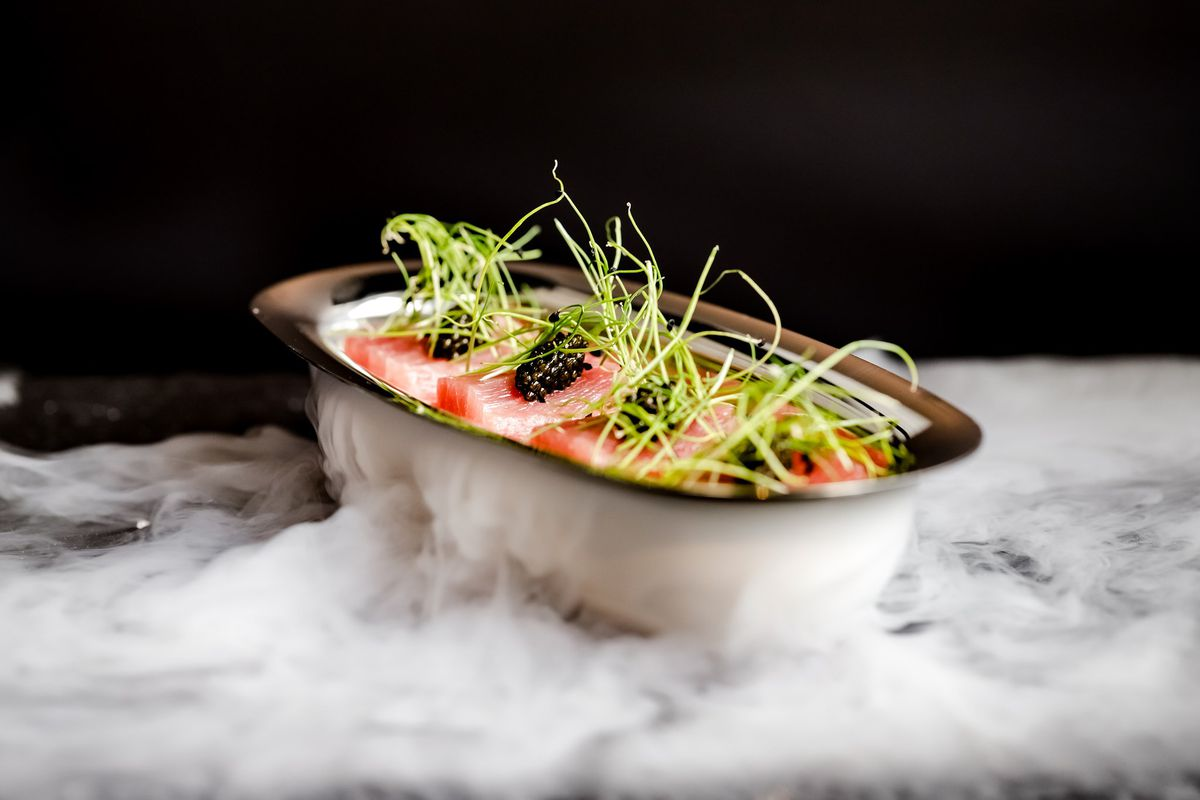 A sashimi dish served in a metal, bowl-shaped vessel, garnished with microgreens.