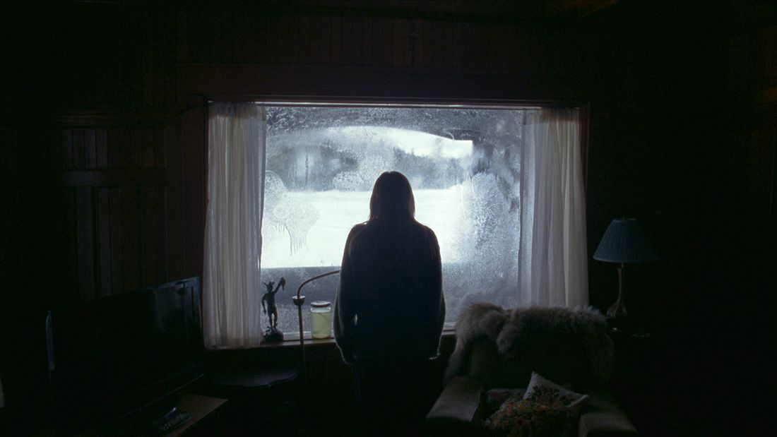 Grace (Riley Keough) looks out at a blizzard caking the lawn with snow in the lodge