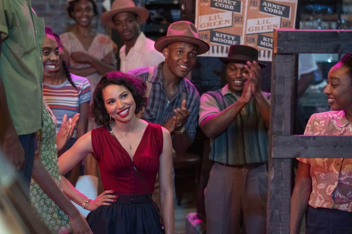 Jurnee Smollett stands smiling in a crowd of applauding people in Lovecraft Country.