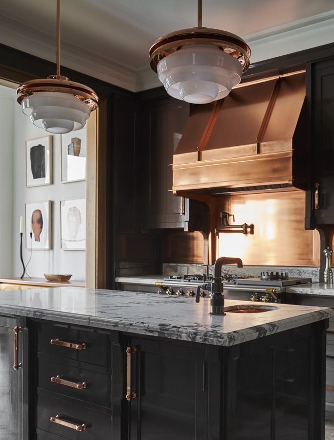 A view of the kitchen island features black cabinetry, copper cabinet pulls and dramatic marble countertops.