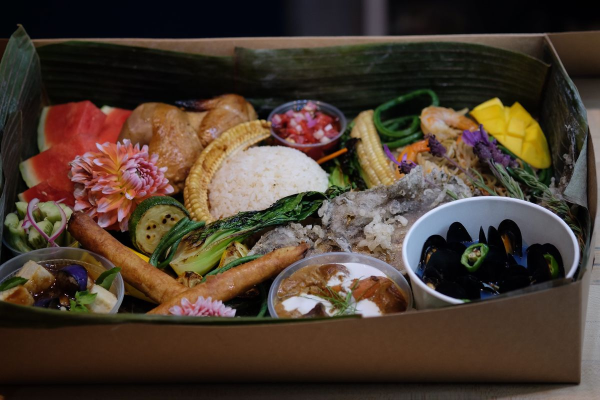 July's kamayan feast, including lumpia, double-fried fish, and mussels, all packed into a half-sheet cake box lined with banana leaves
