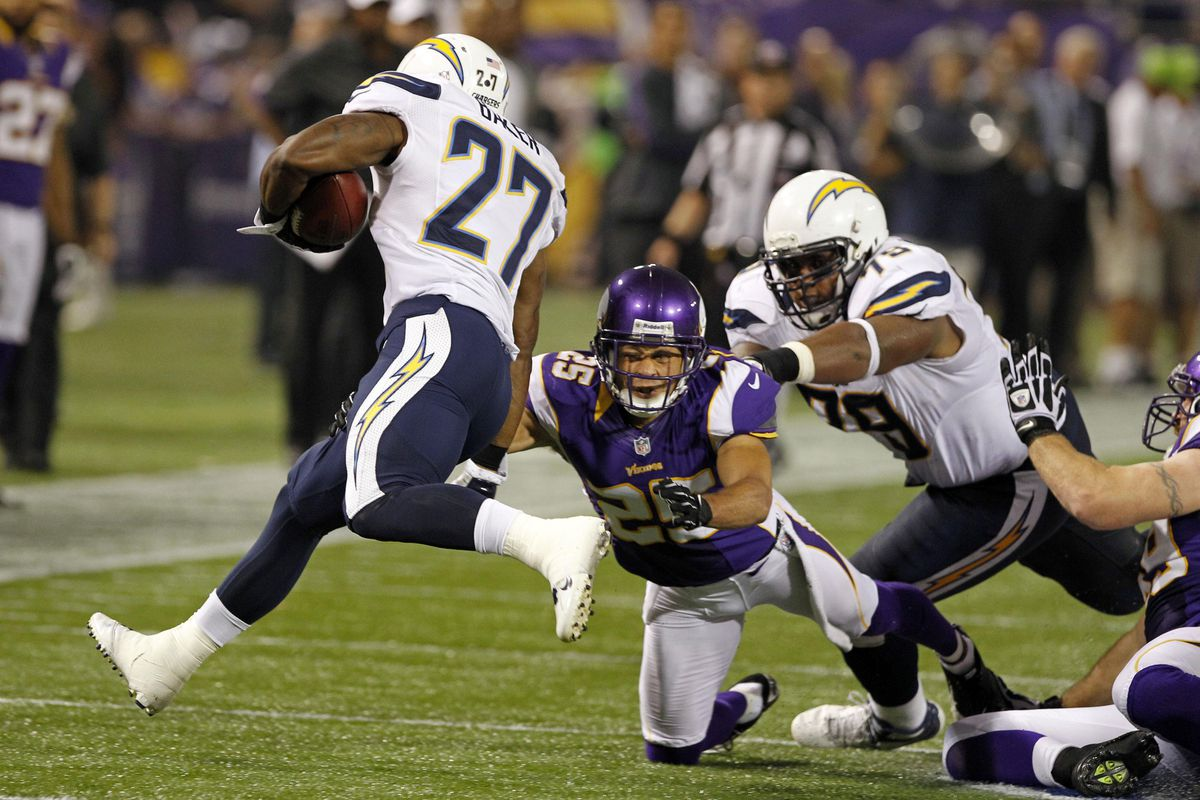 Minnesota Vikings cornerback Chris Carr (25) pushes San Diego Chargers running back Edwin Baker (27) out of bounds for a 2 yard gain as tackle Mike Harris (79) assists